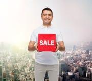 Glimlachende mens met verkoopsigh omhoog over stadsachtergrond Royalty-vrije Stock Fotografie