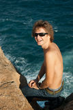 Glimlachende mens op de rots Stock Afbeeldingen