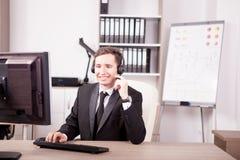 Glimlachende mens van de steun die van de Klantendienst in het bureau werken stock afbeelding