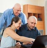 Glimlachende mensen aan het werk aangaande laptop Royalty-vrije Stock Foto's