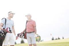 Glimlachende mensen die bij golfcursus tegen duidelijke hemel spreken Royalty-vrije Stock Afbeelding