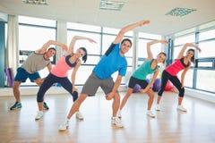 Glimlachende mensen die de oefening van de machtsgeschiktheid doen bij yogaklasse Stock Afbeeldingen
