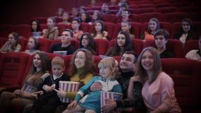 Glimlachende mensen die op film in bioskoop letten stock video
