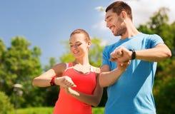 Glimlachende mensen met de horloges van het harttarief in openlucht Royalty-vrije Stock Fotografie