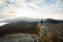 Glimlachende mensenwandelaar met rugzak die en op de bovenkant van de berg situeren ontspannen en de mooie gele herfst bekijken Stock Foto's