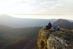 Glimlachende mensenwandelaar met rugzak die en op de bovenkant van de berg situeren ontspannen en de mooie gele herfst bekijken Royalty-vrije Stock Afbeeldingen