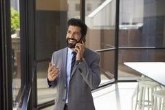 Glimlachende midden oude Spaanse zakenman op telefoon in bureau royalty-vrije stock foto's