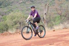 Glimlachende midden oude vrouw die in openlucht van rit genieten bij Berg Bik stock fotografie