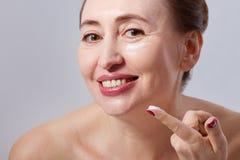Glimlachende Midden oude vrouw met witte room op gezicht en vinger op grijze achtergrond Exemplaarruimte en spot omhoog Selectiev Royalty-vrije Stock Foto's