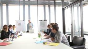 Glimlachende middenleeftijds creatieve directeur die op een vergadering met collega's bespreken stock video