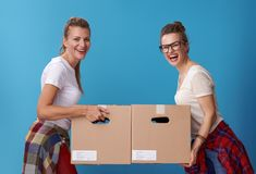 Glimlachende moderne vrouwelijke kamergenoten met kartondozen op blauw royalty-vrije stock foto