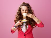 Glimlachende modieuze vrouw op roze achtergrond met kop van koffie Royalty-vrije Stock Afbeeldingen