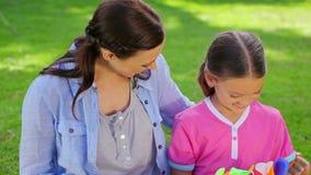 Glimlachende moeder die een vlieger geven aan haar dochter stock videobeelden