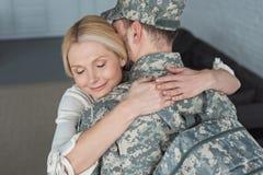 glimlachende moeder die gekweekte zoon in militaire eenvormig koesteren royalty-vrije stock afbeeldingen
