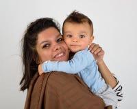 Glimlachende moeder die haar baby houdt royalty-vrije stock fotografie