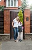 Glimlachende moeder die haar dochter koesteren die naar school gaan voor Royalty-vrije Stock Foto's