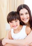 Glimlachende moeder die haar zoon koestert Stock Fotografie