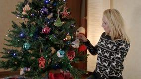 Glimlachende moeder die Kerstmisboom in woonkamer verfraaien stock footage