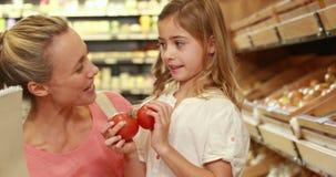 Glimlachende moeder die met haar twee kinderen winkelen stock videobeelden