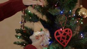 Glimlachende moeder die Toy Santa Claus op de Kerstboom hangen stock videobeelden