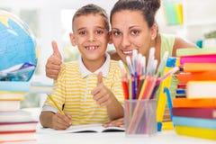 Glimlachende moeder die zoon helpen om zijn thuiswerk te doen Stock Fotografie