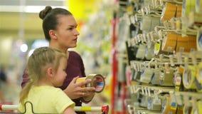 Glimlachende moeder en dochter bij de supermarkt Een Dochter helpt Haar Moeder een Plakband kiezen Cutiedochter stock footage