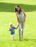 Glimlachende moeder en dochter die op gras lopen Stock Afbeeldingen