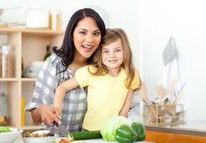 Glimlachende moeder en dochter scherpe groenten Royalty-vrije Stock Afbeeldingen