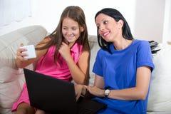Glimlachende moeder en haar dochter die een notitieboekje gebruiken Stock Afbeeldingen