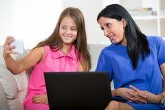 Glimlachende moeder en haar dochter die een notitieboekje gebruiken Stock Foto