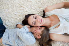 Glimlachende moeder en haar dochter die op de vloer liggen Stock Fotografie
