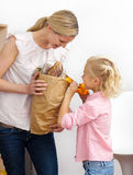 Glimlachende moeder en haar het uitpakken van het Meisje Stock Afbeelding