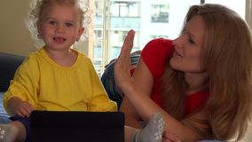 Glimlachende moeder en haar leuke peuterdochter die tablet thuis gebruiken stock footage