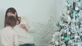 Glimlachende moeder en haar zoon die Kerstboom in de woonkamer verfraaien stock video