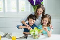 Glimlachende moeder en van kinderen het mengen zich kom salade in keuken stock foto's