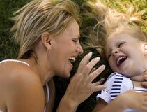 Glimlachende moeder en weinig dochter op aard. Gelukkige mensen in openlucht Royalty-vrije Stock Foto's