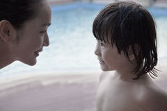 Glimlachende moeder en zoon face to face door de pool Royalty-vrije Stock Foto