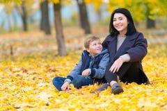 Glimlachende moeder en zoonszitting in dalingsbladeren stock fotografie