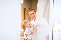 Glimlachende moeder met baby het kijken uit van venster Stock Afbeeldingen