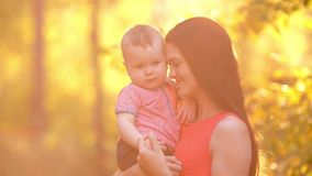 Glimlachende moeder met baby op zonsondergang stock videobeelden