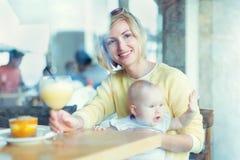 Glimlachende moeder met babymeisje het kijken door het venster Stock Foto's