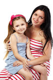 Glimlachende moeder met dochter op haar knieën Stock Fotografie