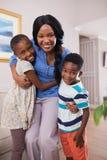 Glimlachende moeder met kinderen thuis stock fotografie