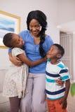 Glimlachende moeder met kinderen in woonkamer royalty-vrije stock fotografie