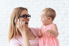 Glimlachende moeder met weinig baby die smartphone gebruiken royalty-vrije stock foto