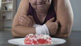 Glimlachende mollige mens die op de vloer liggen en doughnut met liefde, het op dieet zijn bekijken stock footage