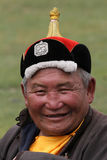 Glimlachende Mongoolse mens met een traditionele hoed stock fotografie