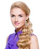Glimlachende mooie blonde vrouw met lang krullend haar Royalty-vrije Stock Foto's