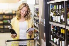 Glimlachende mooie blondevrouw die een wijnfles in haar hand hebben en een blocnote bekijken Royalty-vrije Stock Afbeelding