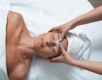 Glimlachende mooie dame die gezichts van massage genieten bij kuuroordsalon royalty-vrije stock fotografie